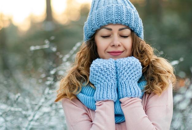 니트 스카프를 입고 젊은 아름 다운 곱슬 갈색 머리 여자