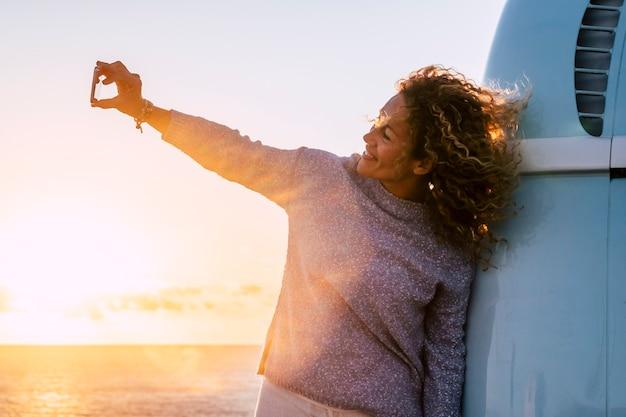 젊은 아름다운 곱슬 쾌활한 여자가 바다 앞에서 일몰 동안 셀카 사진을 찍습니다.
