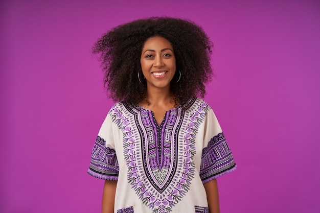 Молодая красивая кудрявая темнокожая женщина в повседневной одежде изолирована, стоя на фиолетовом и держа руки вдоль тела, счастливо с очаровательной улыбкой