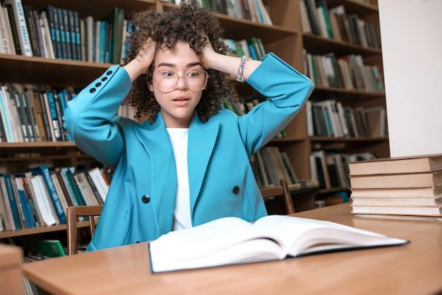 メガネと図書館で本を座っている青いスーツの美しい巻き毛の少女。