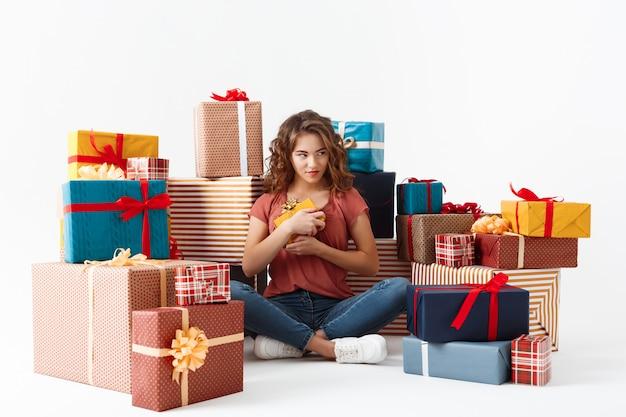 선물 상자 중 바닥에 앉아 아름 다운 곱슬 소녀 격리 됨