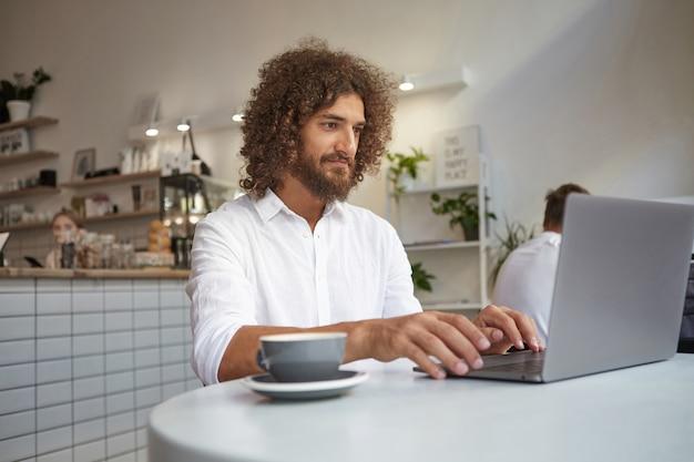 Libero professionista maschio bello riccio giovane seduto nella caffetteria con laptop e tazza di caffè al tavolo, indossa una camicia bianca, guardando lo schermo con un sorriso morbido