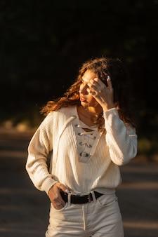 니트 블라우스를 입은 젊고 아름다운 곱슬머리 여성 모델은 해질녘 공원을 산책한다