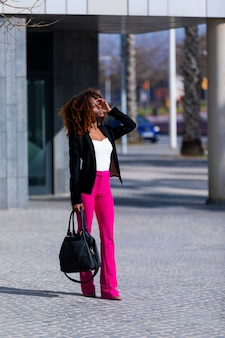 Young beautiful curly woman wearing elegant clothes and handbag while standing in the street in sunny day