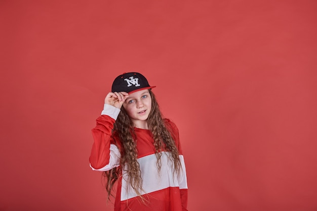 Young beautiful cute girl dancing on red wall, modern slim hip-hop style teenage girl jumping