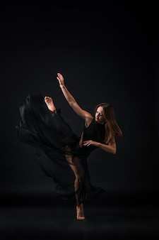 Young beautiful dancer in beige dress dancing on black wall
