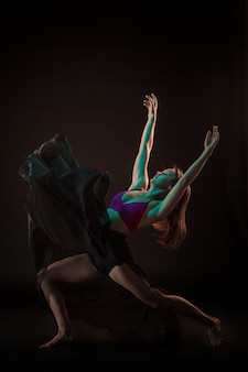 Young beautiful dancer in beige dress dancing on black wall