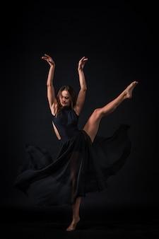 Young beautiful dancer in beige dress dancing on black