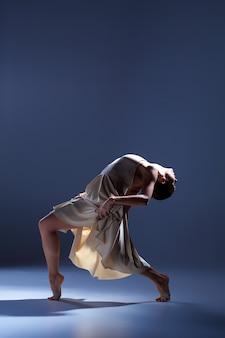 Young beautiful dancer in beige dress dancing on gray studio background