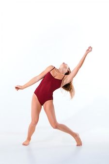 Young beautiful dancer in beige dress dancing on white wall