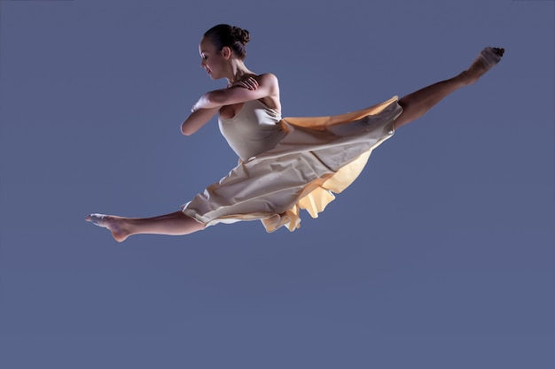 Young beautiful dancer in beige dress jumping on gray studio background