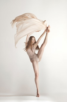 Young beautiful dancer in beige swimsuit dancing on gray