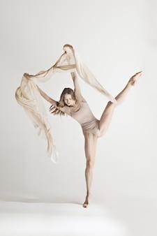 Young beautiful dancer in beige swimsuit dancing