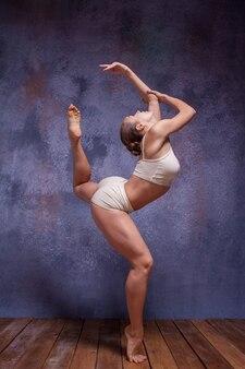 Young beautiful dancer in beige swimwear dancing on lilac studio background on wooden floor