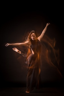Young beautiful dancer dancing on black wall