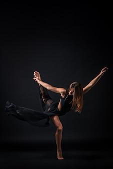 Молодая красивая танцовщица в бежевом платье танцует на черном фоне
