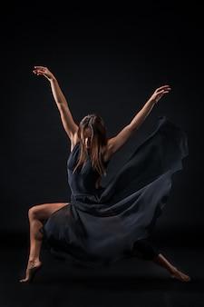 Молодая красивая танцовщица в бежевом платье танцует на черной стене