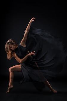 Молодая красивая танцовщица в бежевом платье танцует на черном