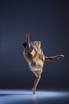 灰色の背景で踊るベージュのドレスの若い美しいダンサー
