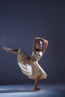 회색 스튜디오 배경에서 춤을 추는 베이지색 드레스를 입은 젊은 아름다운 댄서
