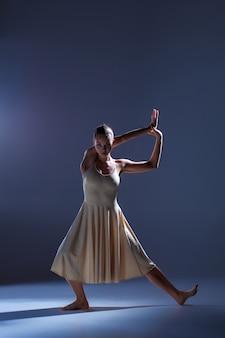 灰色のスタジオの背景に踊るベージュのドレスの若い美しいダンサー