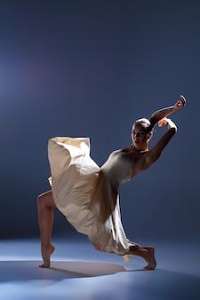 Молодая красивая танцовщица в бежевом платье танцует на сером студийном фоне