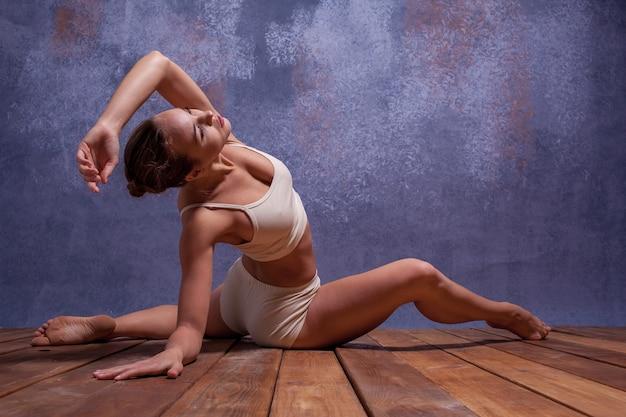 ライラックの背景に踊るベージュの水着の若い美しいダンサー