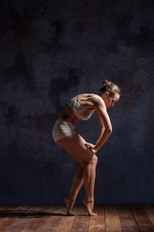 나무 바닥에 라일락 스튜디오 배경에서 춤 베이지색 수영복에 젊은 아름 다운 댄서