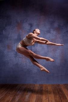 木製の床のライラックスタジオの背景に踊るベージュの水着の若い美しいダンサー