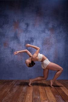 Молодая красивая танцовщица в бежевых купальниках танцует на сиреневом фоне студии на деревянном полу