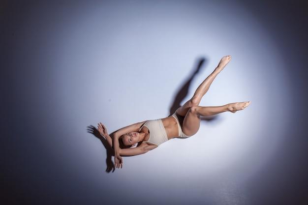 ライラックスタジオの背景に踊るベージュの水着の若い美しいダンサー