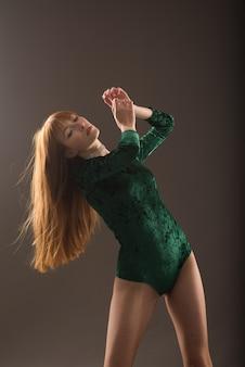 Молодая красивая танцовщица позирует в студии на сером фоне