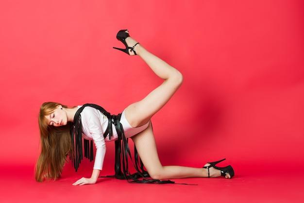 Молодая красивая танцовщица позирует в студии на красном фоне