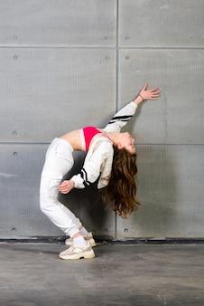 スタジオの背景にポーズをとる若い美しいダンサー