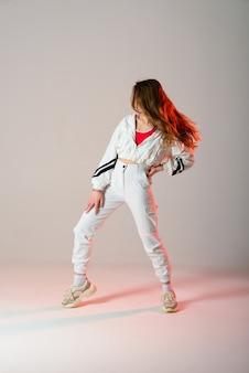 Молодая красивая танцовщица позирует на фоне студии