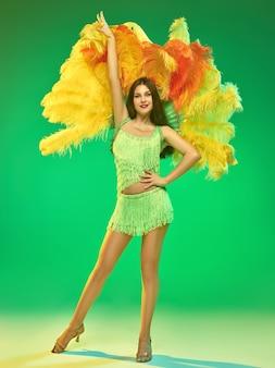 Молодая красивая танцовщица позирует на зеленой стене
