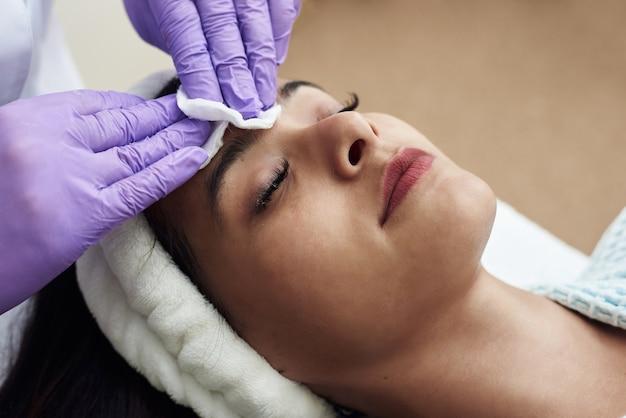 Молодая красивая темноволосая женщина лежит в кабинете косметолога и делает пилинг лица