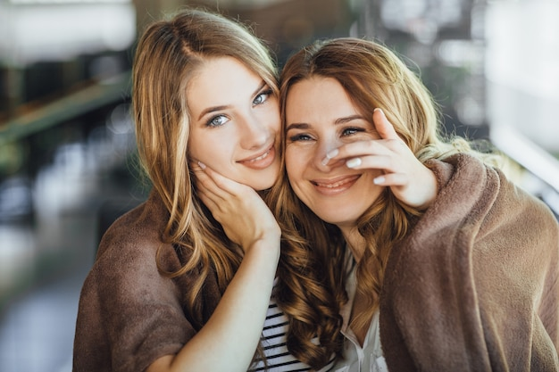 Молодая красивая дочка блондинки и ее мама средних лет обнимаются и радуются на летней террасе современного кафе.
