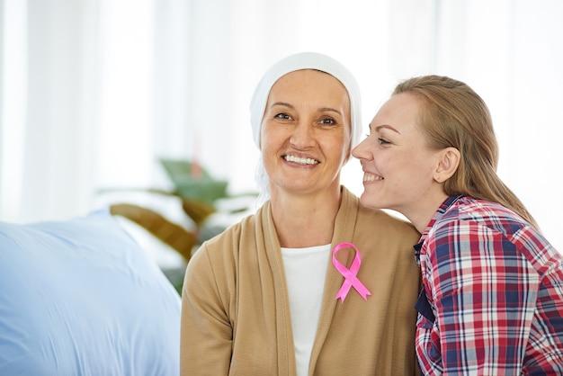 Молодая красивая дочь сидит рядом с матерью, которая борется с раком, чтобы поддержать ее на больничной койке