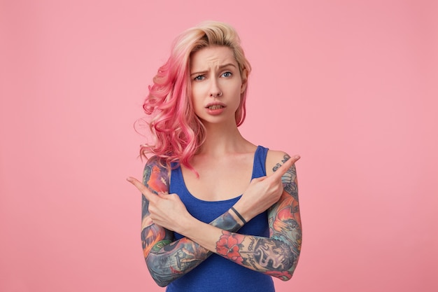 Young beautiful disconnected pink haired lady in blue t-shirt, confused and can not understand which way she needs, arms crossed, points fingers in different directions, stands.