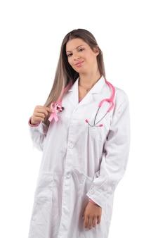 Молодая красивая женщина-врач с розовым стетоскопом и розовой лентой осведомленности для рака груди.
