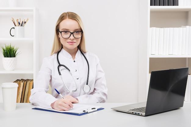 Молодая красивая женщина-врач работает счастливой и улыбается в больнице, сидя на столе, медицинская концепция