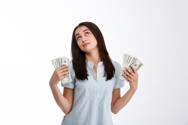 Young beautiful dreamy looking up business girl holding money in both hands over white wall