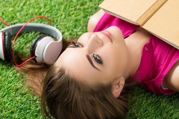 Молодая красивая мечтательная женщина, лежащая на траве в парке с книгой и наушниками рядом с ней.
