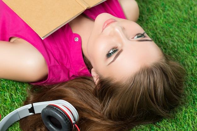 本と彼女の横にあるヘッドフォンで公園の芝生の上に敷設若い美しい夢のような女性。