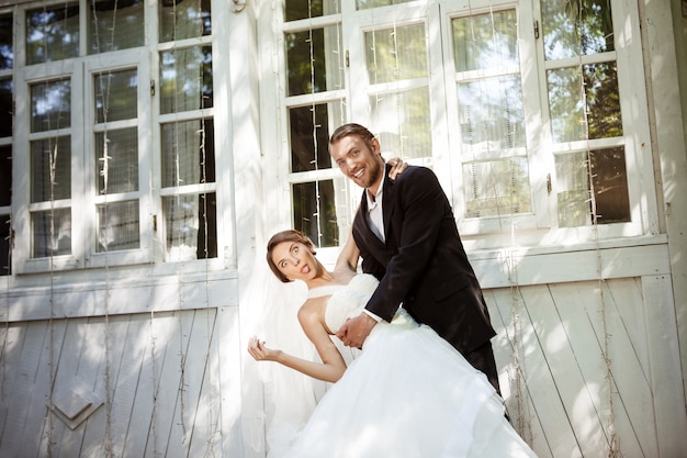 Young beautiful dressy newlyweds smiling, fooling, dancing outdoors.