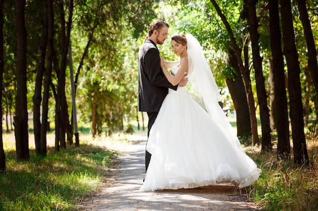 Young beautiful dressy newlyweds smiling, posing, embracing in park.