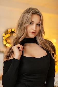파티에서 황금빛 보케를 배경으로 한 세련된 검은색 드레스를 입은 젊고 우아한 여성 모델입니다. 겨울 방학