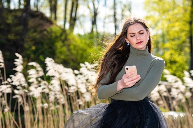 彼女はスマートフォンでメッセージを読んだとき若い美しい感情的なブルネットの女性は悲しい感じ