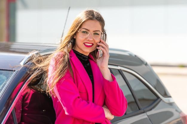 若い美しい感情的な実業家が車から降りて、電話で協議